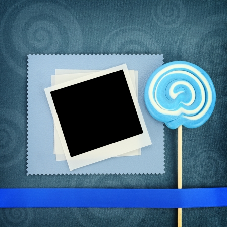 Photo frame and lollipop on blue background photo