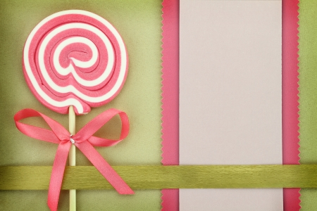 Blank banner with lollipop on green background photo