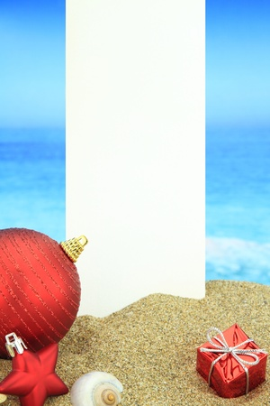 tropical border: White banner and Christmas ornaments on the beach