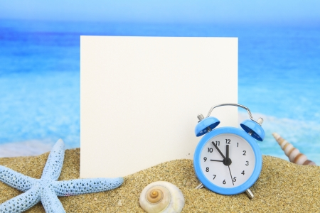 time frame: Summer time. Paper card and alarm clock on the beach