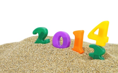 Multicolored new year 2014 on the sand photo
