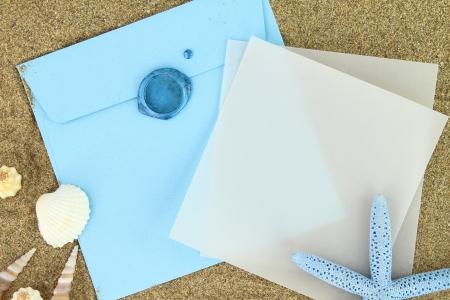 boda en la playa: Tarjeta de papel y un sobre azul en la playa Foto de archivo