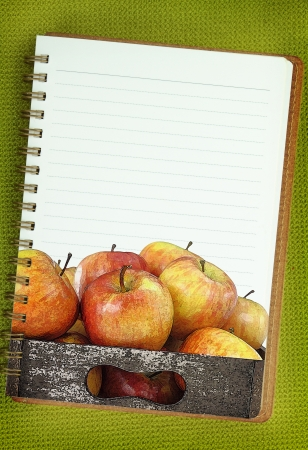 Wooden box full of apples painting on blank notebook page photo