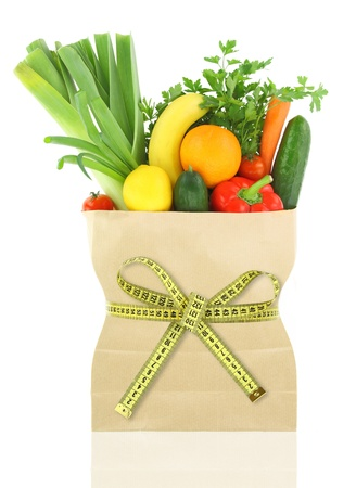 light diet: Fresh vegetables and fruits in a paper grocery bag with measuring tape  Stock Photo