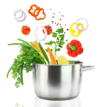 ustensiles de cuisine: Les légumes frais de tomber dans une cocotte en acier inoxydable Banque d'images