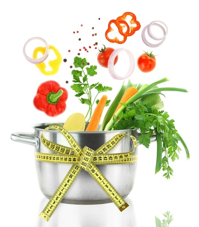 lose balance: Fresh vegetables falling into a casserole pot with measuring tape