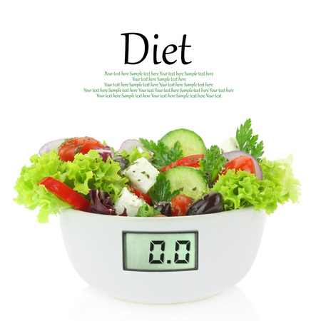 Diet meal. Vegetables salad in a bowl with digital weight scale  photo
