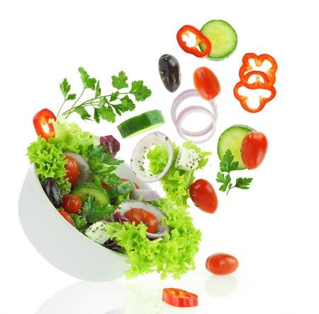 Verduras frescas mezcladas caer en un plato de ensalada Foto de archivo