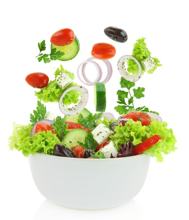 greek chef: Fresh mixed vegetables falling into a bowl of salad  Stock Photo