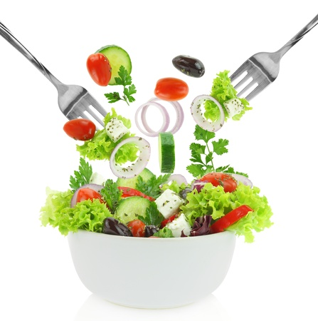 Fresh mixed vegetables falling into a bowl of salad  Stock Photo