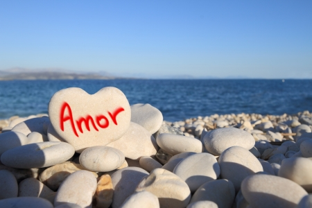 written on heart shaped stone on the beach photo