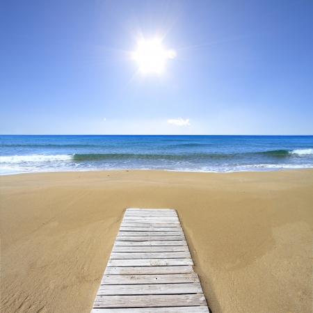 huir: Piso de madera en la playa de arena dorada Foto de archivo