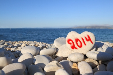 2014  new year written on heart shaped stone on the beach with spray brush photo