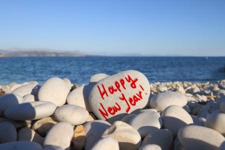 beach happy new year: Happy new year written on heart shaped stone on the beach with spray brush Stock Photo