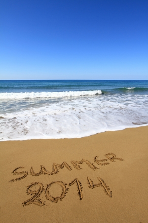 �Summer 2014� written on sandy beach photo