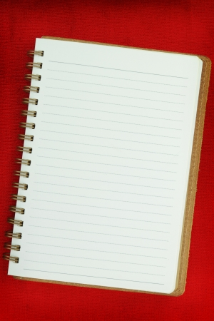 White Blank notebook on red background photo