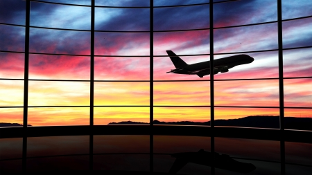 terminal: Airport window with airplane flying at sunset  Stock Photo