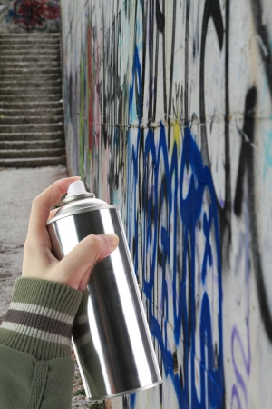 Human hand holding a graffiti Spray can in front of a colorful wall photo