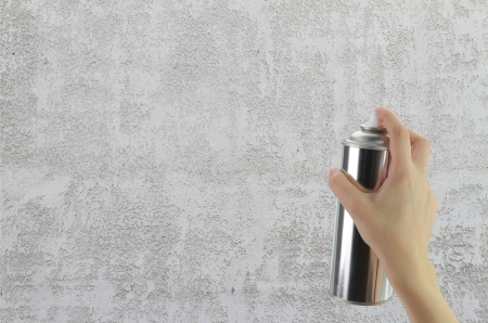 Human hand holding a graffiti Spray can in front of blank concrete wall photo