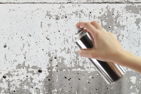 aerosol can: Human hand holding a graffiti Spray can in front of blank concrete wall