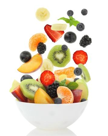 ensalada de frutas: Ensalada de fruta mezclada fresca que cae en un plato de ensalada Foto de archivo
