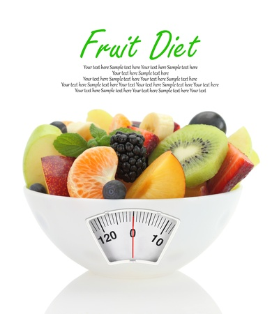 Diet meal. Fruit salad in a bowl with weight scale photo