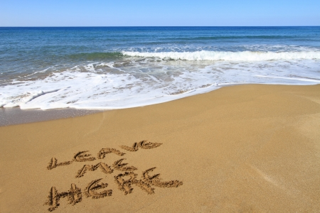 Leave me here written on golden sandy beach photo