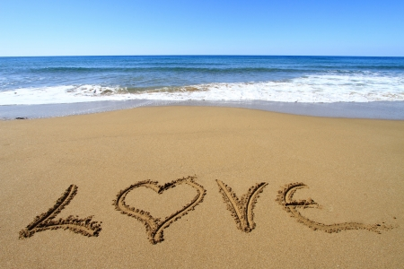 anniversary beach: Love written on golden sandy beach Stock Photo