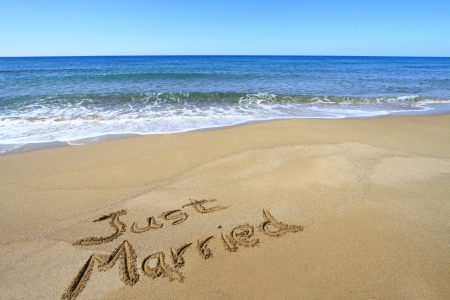 anniversary beach: Just married written on golden sandy beach
