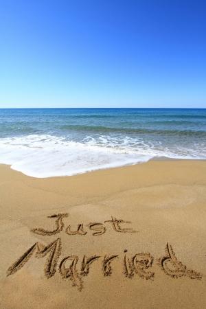 """""""Just married"""" auf goldenen Sandstrand geschrieben"""