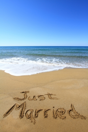 tourist destination: Just married written on golden sandy beach