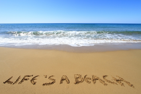 Life is a beach written on golden sandy beach photo