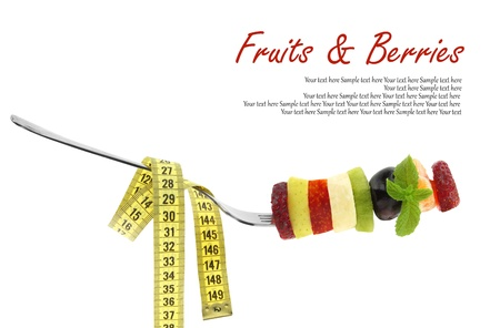 Fresh mixed slices of fruits on a fork with measuring tape photo
