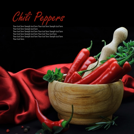 hot peppers: Red hot chili peppers with herbs in wooden  Stock Photo