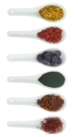 Superfoods in porcelain spoons. Pollen, goji berries, blueberries, spirulina, Hippophae and saffron photo