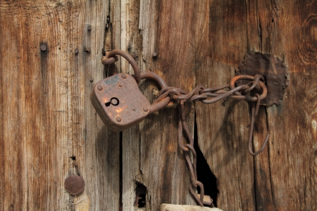 Old rusty padlock with chain on wooden door photo