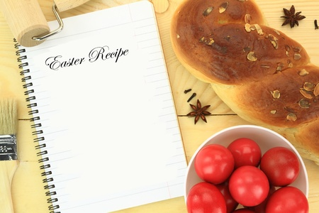 Easter sweet bread with red eggs and recipe book on the table