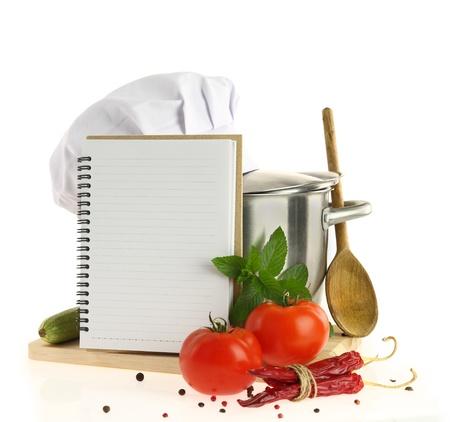 Kookboek, groenten en braadpan geïsoleerd op wit Stockfoto