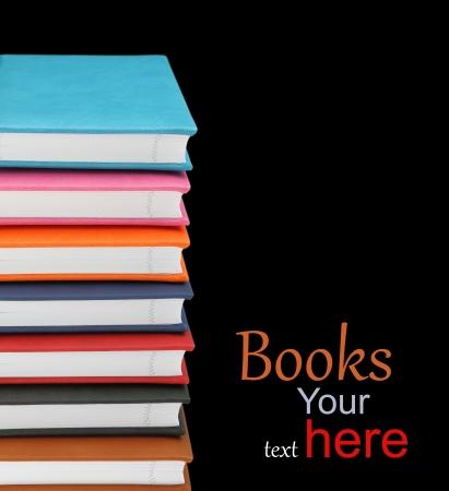 writing book: Pila di libri colorati su sfondo nero Archivio Fotografico