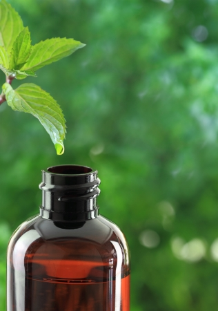 balm: Drop falling of mint leaf in an essential oil bottle