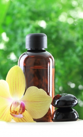 aromatherapy oil: Bottle of essential oil with orchid flower and zen stones Stock Photo