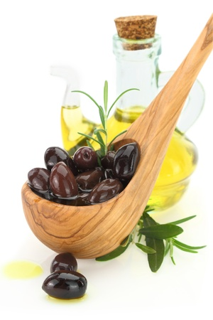 kalamata: Olives in a wooden spoon and a bottle of virgin olive oil on white background  Stock Photo