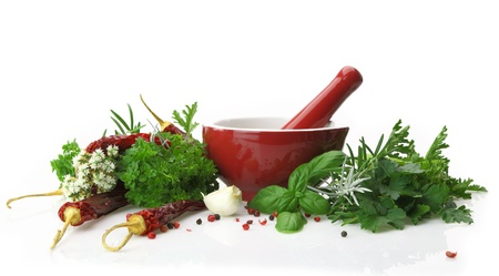ingredient: Red porcelain mortar and pestle with fresh herbs Stock Photo