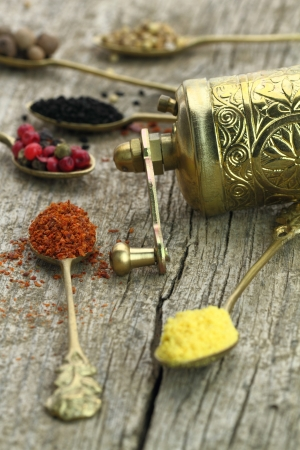 pepper grinder: Old spoons with spices and pepper grinder on wooden background