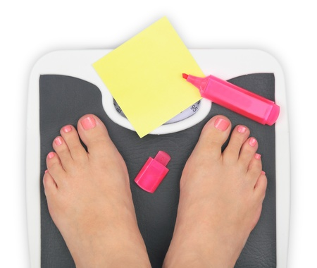 Woman s feet on bathroom scale and blank notepaper photo