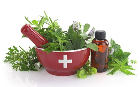 Mortar with medicine cross, fresh herbs and essential oil bottle Stock Photo