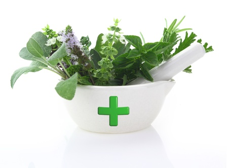 Porcelain mortar with pharmacy cross and fresh herbs photo