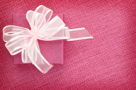 Gift box on pink fabric background