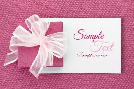 Caja de regalo rosado con la cinta en la tarjeta blanca