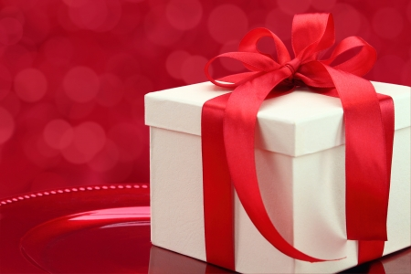 Gift box on a plate with elegant red lights background photo